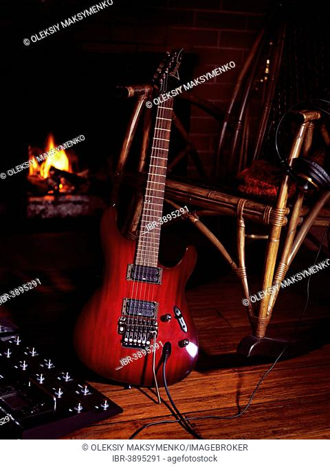 Electric guitar with a guitar processor propped against a rocking chair near a fireplace