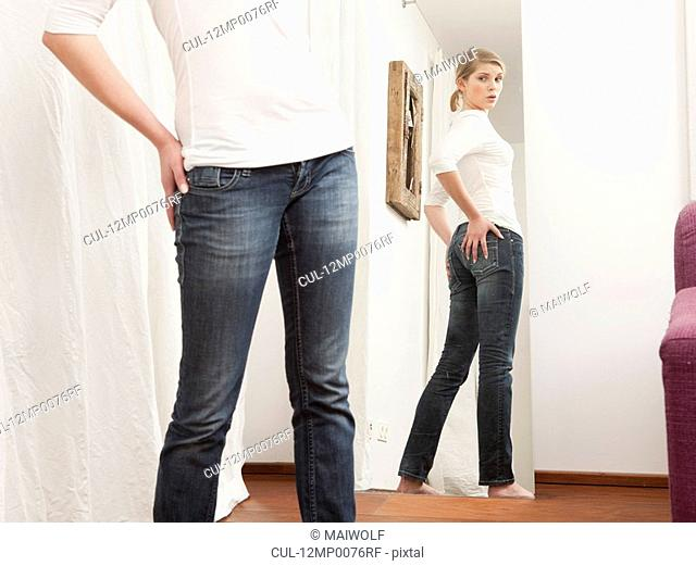 Woman checking her body in the mirror