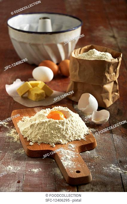 Flour, eggs, butter and a ring-shaped baking tin for a Bundt cake