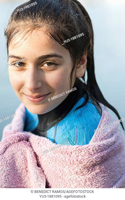 Girl aged 12 in a wetsuit and wrapped in a towel after a swim