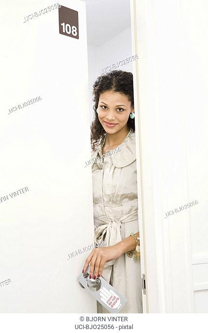 Woman putting Do Not Disturb sign on door