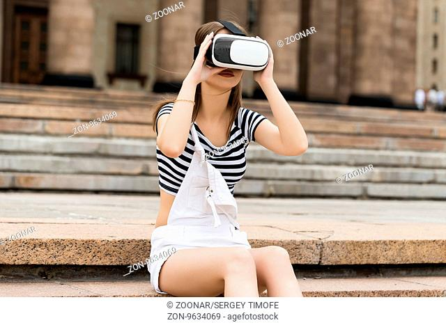 Young girl sitting on the stairs, near the university, in virtual reality in VR