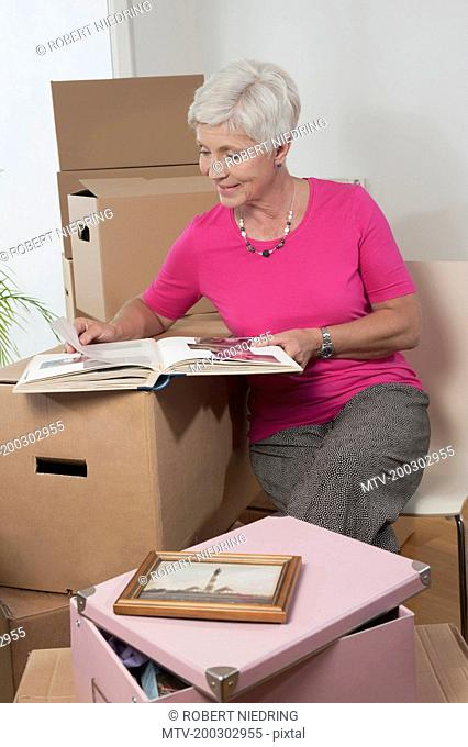 Senior woman looking at photo album in new apartment, Bavaria, Germany