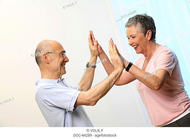 older man and older woman doing gymnastics - seniors