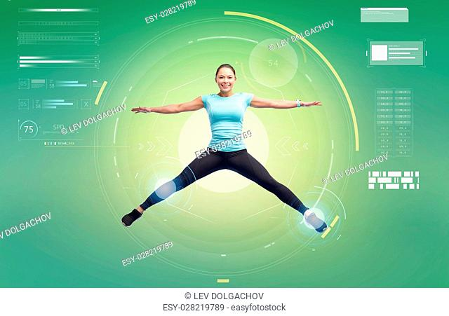 sport, fitness, motion and people concept - happy smiling young woman jumping in air over green background