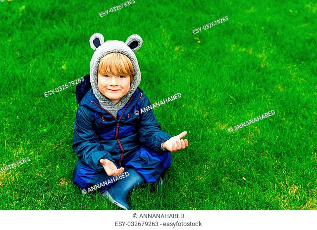 Cute kid resting outdoors, sitting on a lawn, playing on a rainy day, wearing blue waterproof all-in-one suit