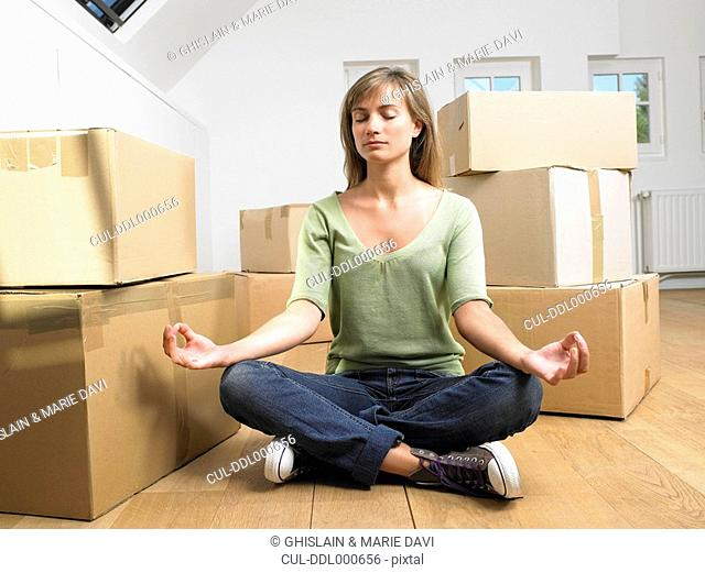 Woman doing yoga with moving boxes around her