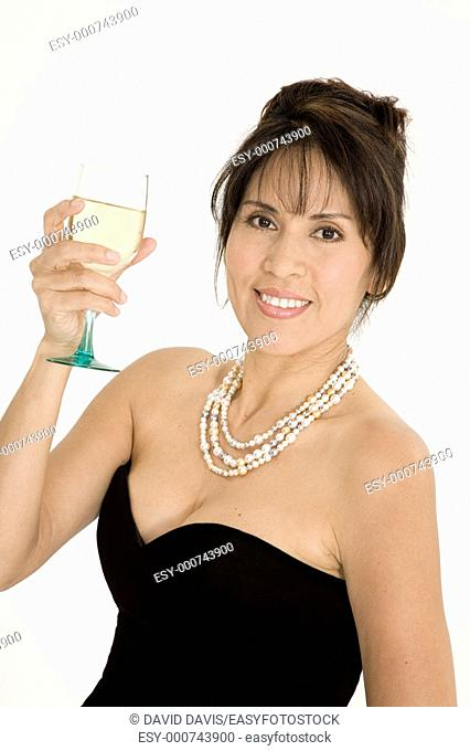Beautiful Brazilian or Hispanic holding a glass of white wine in a black evening gown on a white background