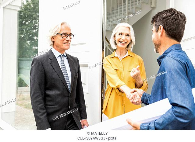 Architect holding rolled up blueprints shaking hands with homeowners at front door smiling