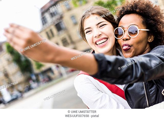 Portrait of two happy best friends taking selfie with smartphone