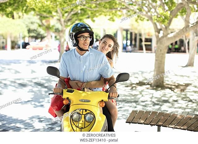 Happy young couple with shopping bags on motor scooter