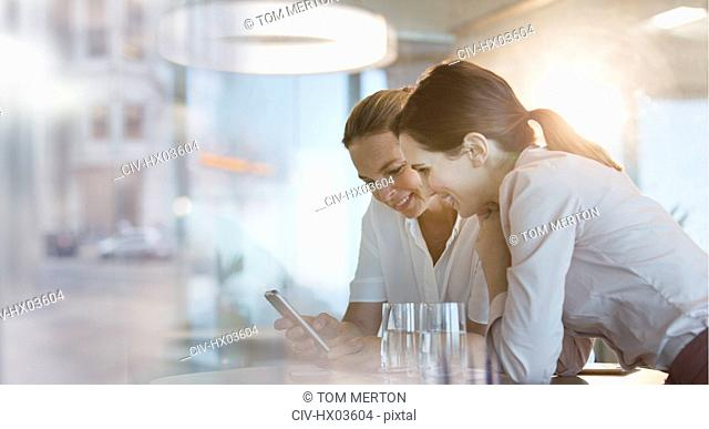 Businesswomen texting with cell phone in office