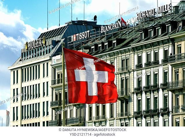 Swiss flag in foreground, in background facades of lake front buildings with famous Swiss brandmarks, Geneva, Switzerland