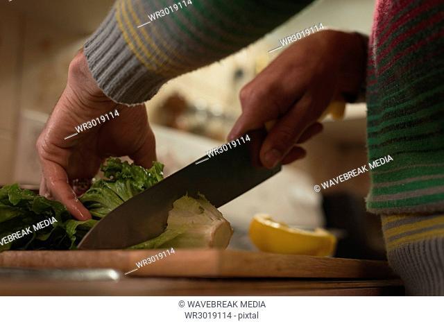 Man cutting leafy vegetable on chopping board