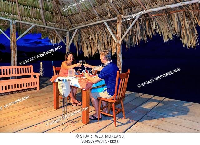 Romantic couple raising a champagne toast at waterfront restaurant, St. Georges Caye, Belize, Central America