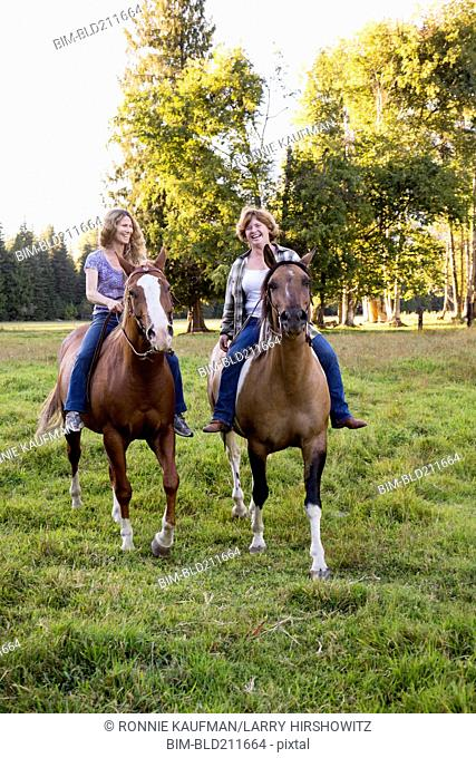 Women riding horses in rural landscape