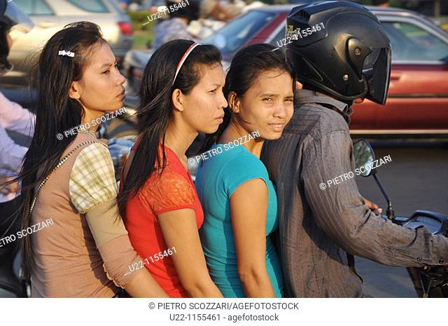 Phnom Penh (Cambodia): three women and a man on a motor-bike