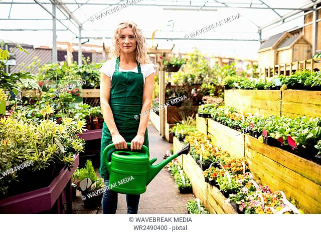 Female florist holding watering can