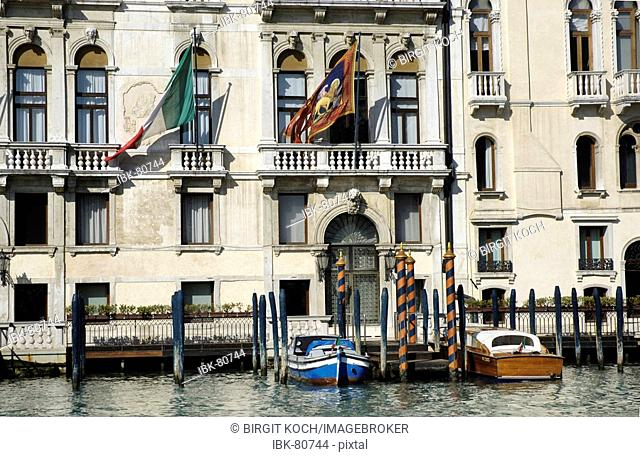 Facade of a house with Italian and venice flag at Canale Grande in Venice Italy