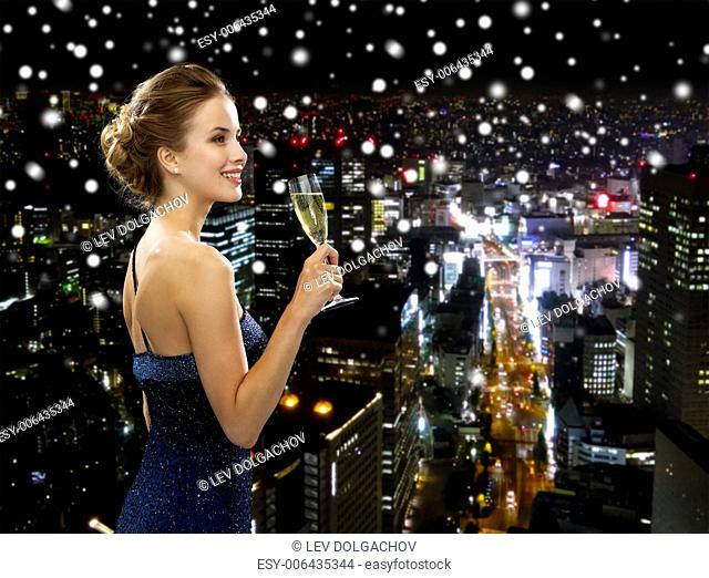 party, drinks, holidays, luxury and celebration concept - smiling woman in evening dress with glass of sparkling wine over snowy night city background