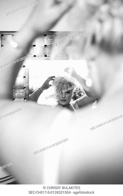 Bride getting ready for her wedding, looking in mirror and fixing her hair