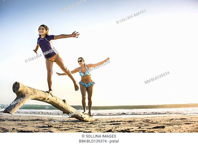 Mother and daughter playing on log on beach