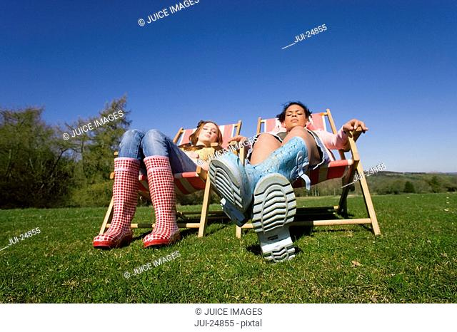 Friends in wellingtons relaxing in lounge chairs in sunny field