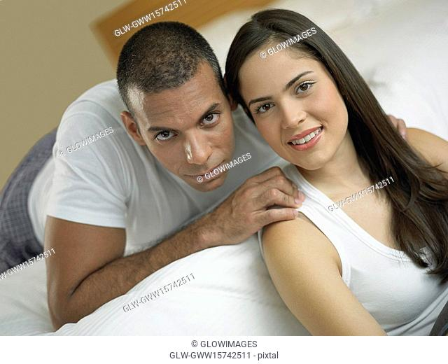 Portrait of a young woman smiling with a mid adult man lying on the bed