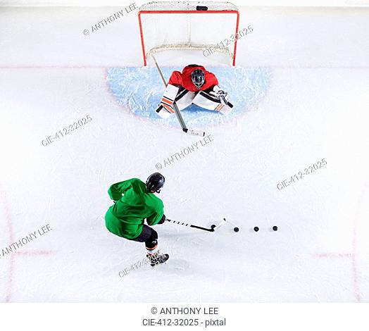 Overhead view hockey player practicing with goalie shooting puck at goal net