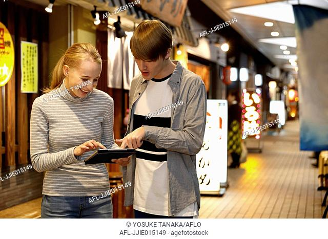 Caucasian tourist couple looking for a restaurant at a traditional shopping street, Tokyo, Japan