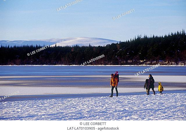 Glenmore. Snow on mountains. Lake,water. Snow on shore. Three people,family in coats