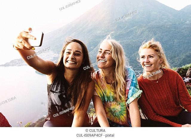 Three female friends taking smartphone selfie at Lake Atitlan, Guatemala