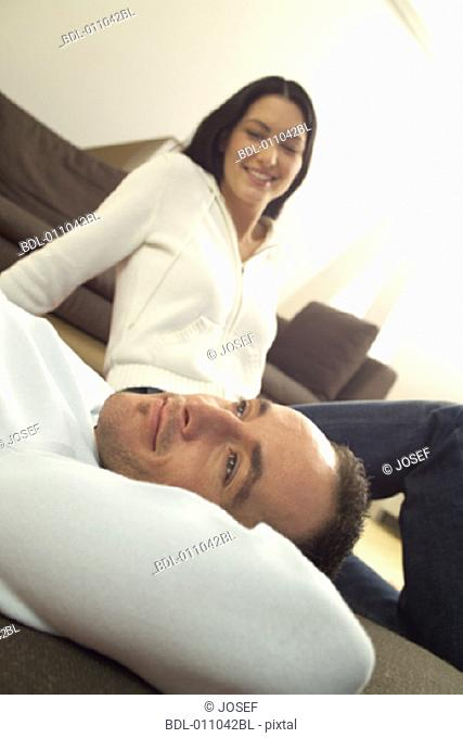 Couple relaxing on the floor of  their living room