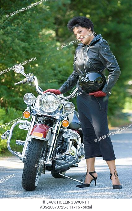 Portrait of a mature woman standing beside a motorcycle and holding a crash helmet