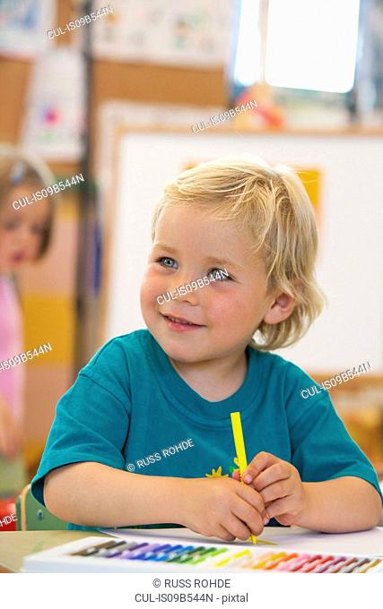 Preschool boy with colouring pen in classroom