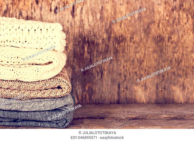A stack of woolen sweater, plaid. Warm clothing. Home atmosphere, winter clothing. Gray, white and brown sweater. Warm and cozy. Knitted clothes