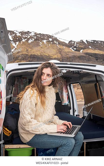 Portrait of young woman sitting in van using laptop