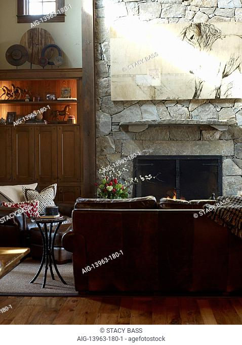 Sofa in front of fire in country style sitting room, USA