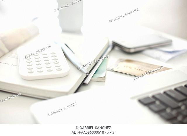 Credit cards and calculator resting near laptop computer in home office