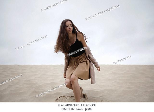 Caucasian woman crouching at beach