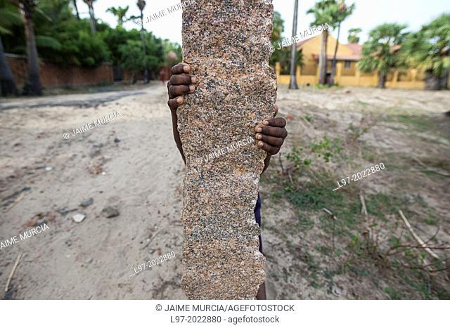 The hands of a young child hiding behind a marble fence post, India