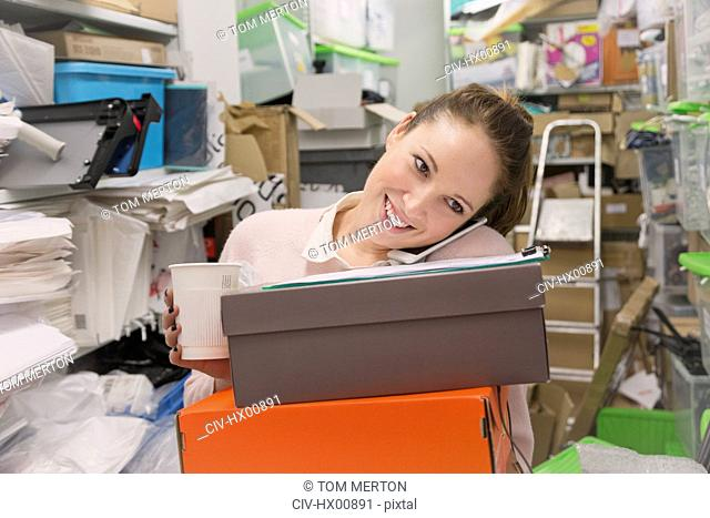 Smiling fashion buyer multitasking carrying shoe boxes, coffee and talking on cell phone