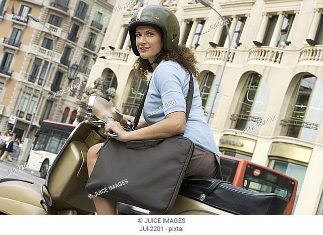 Spain, Barcelona, woman in crash helmet riding moped in city street, carrying bag, portrait tilt