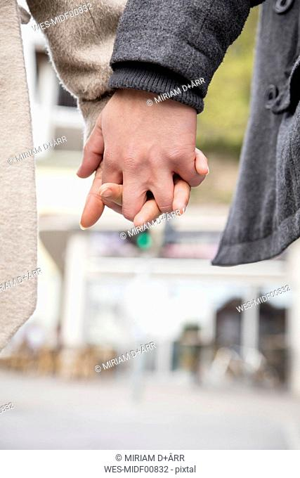 Young couple hand in hand, close-up