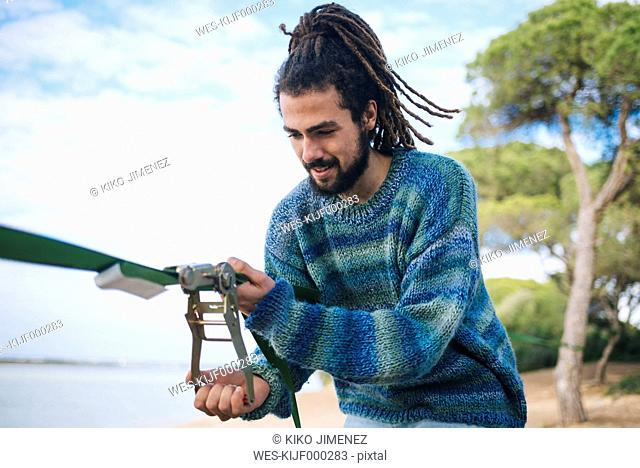 Young man with dreadlocks fixing a slackline