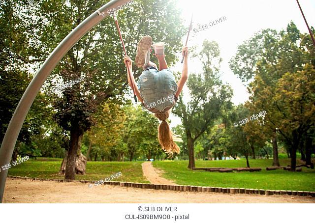 Girl swinging on playground equipment