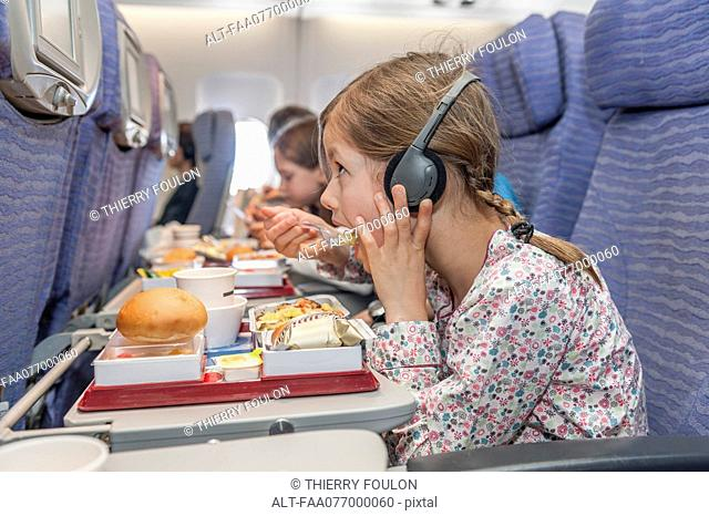 Girl watching movie on airplane while eating airline meal