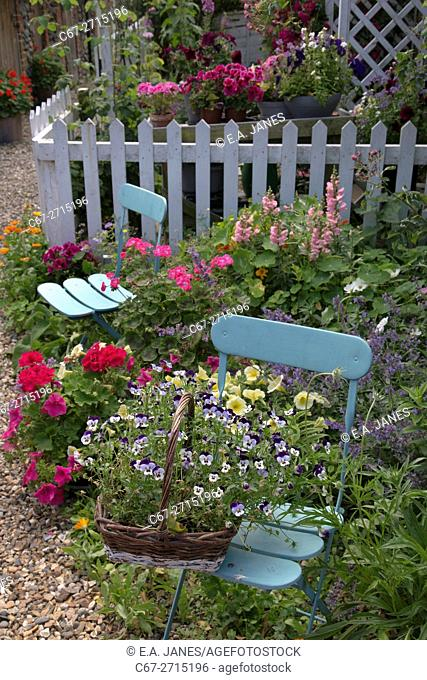 Cottage garden with container planting and blue chairs