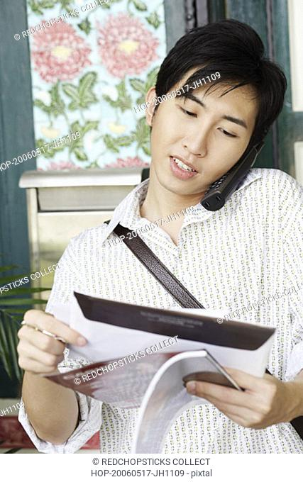 Close-up of a young man reading mail while talking on a cordless phone