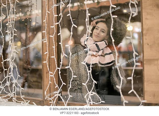 woman with winter scarf behind window, chain of lights, in Munich, Germany